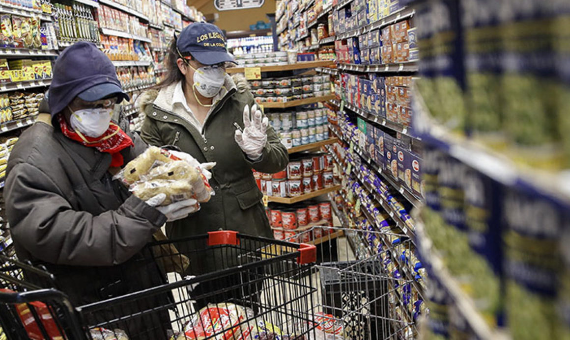 Shoppers fill cart with packaged foods in bulk
